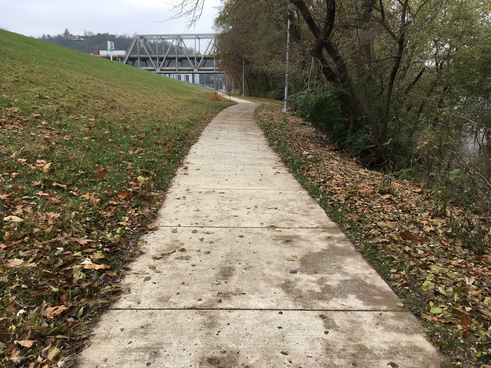 The Riverfront Commons Trail is a perfect example of a Paved Surface Trail. It goes where a road cannot fit, but makes perfect sense for a pedestrian and bike path to connect multiple points along the riverfront.