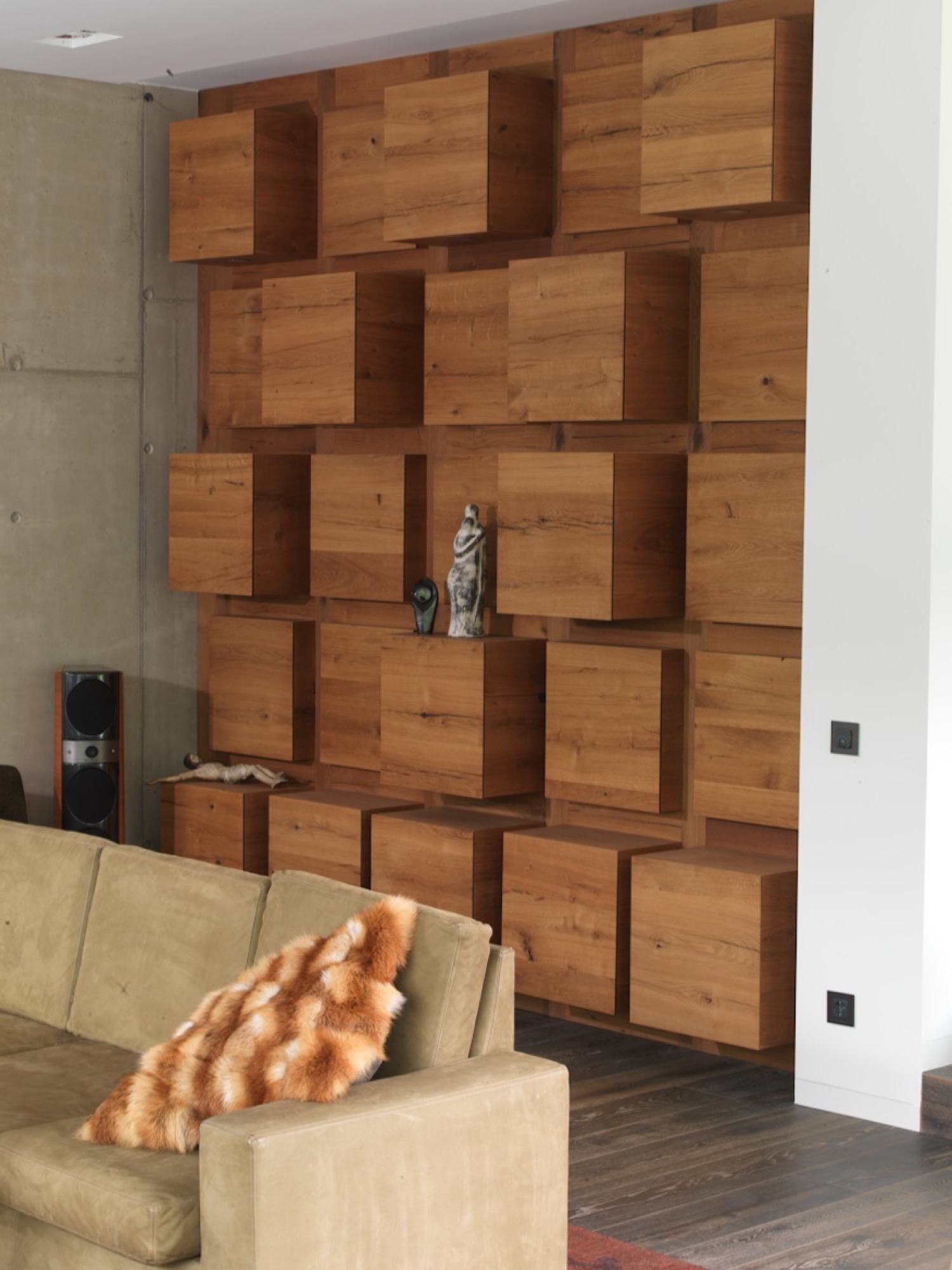 The same wooden cubes serve as armoire and shelving units in the living room and along the facade.