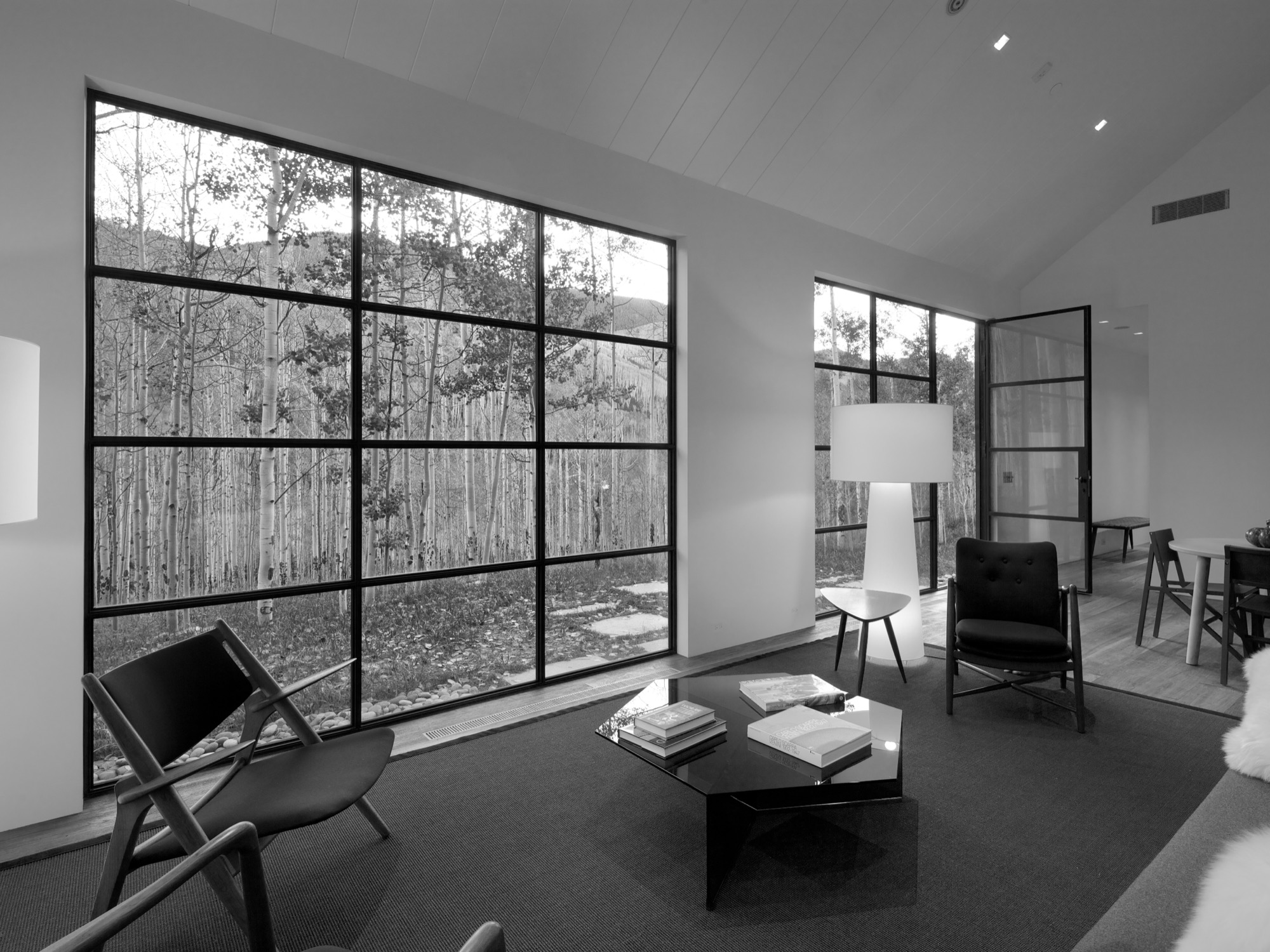 The big window and door in the living room provide a connection to the aspen trees outside / Photo by Greg Watts