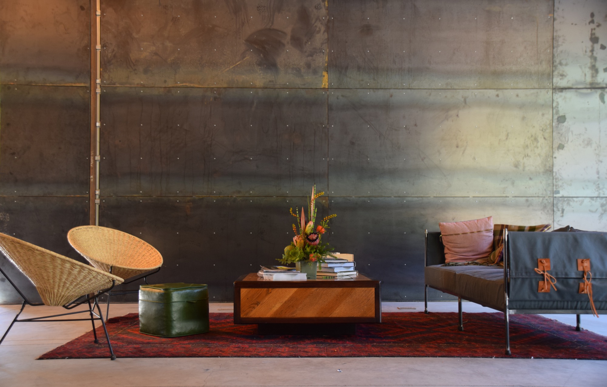 Geremia Design created a texturally rich lounge area, its wood, leather, and textile elements softening the steel backdrop / Photo by Emma Geiszler