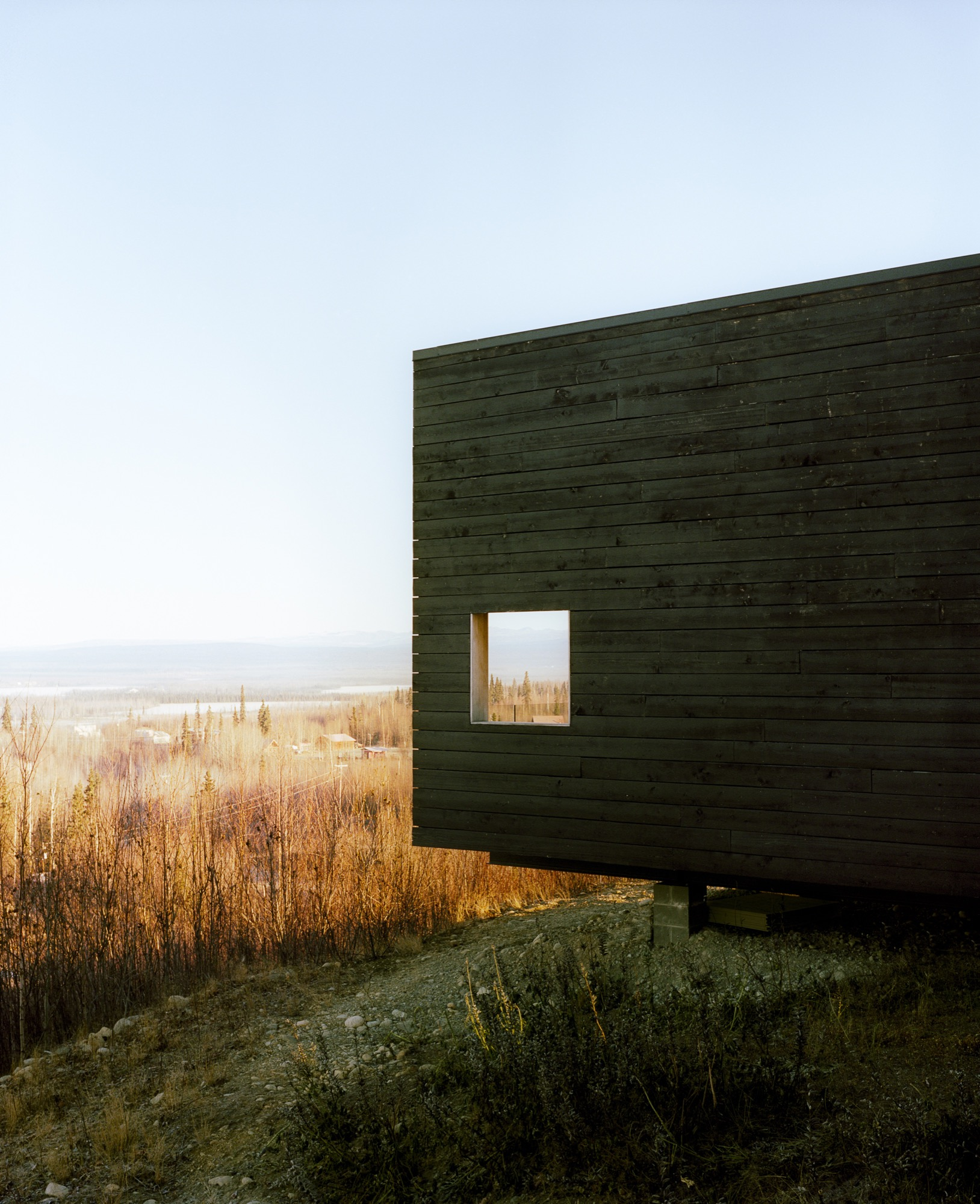The charred cedar exterior gently basks in the Alaskan sun / Photo by Kamil Bialous
