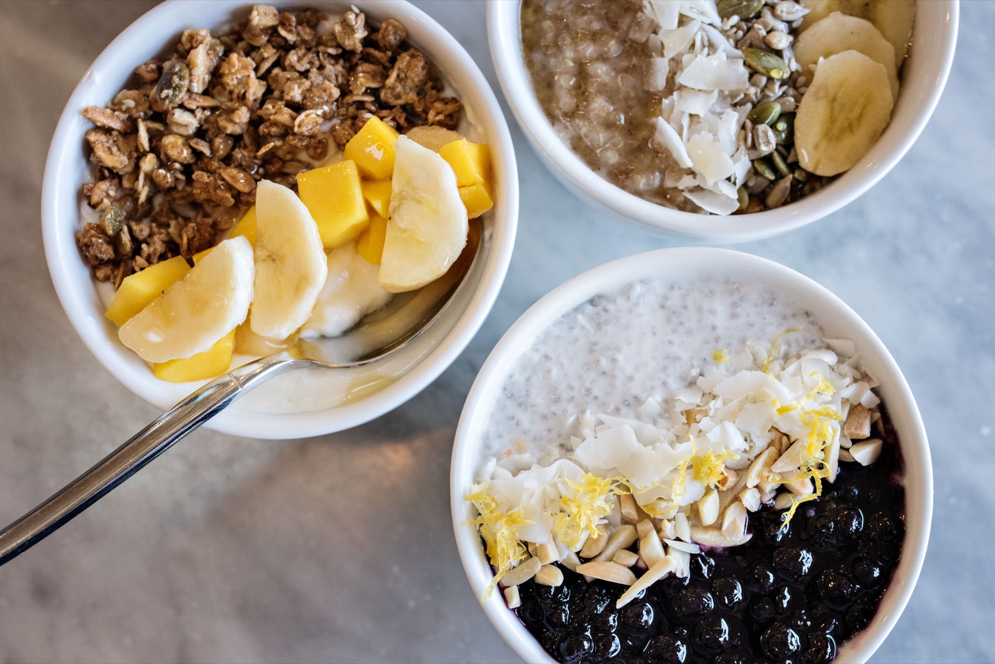 L to R: Müsli B with seasonal fruit / Quinoa Porridge with coconut flakes, toasted seeds and banana / Coconut Chia Seed Pudding with coconut flakes, crushed almonds, and blueberry-lemon compote / Photo by D'Ann McCormick Boal