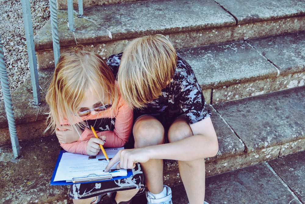 children on front steps looking at book