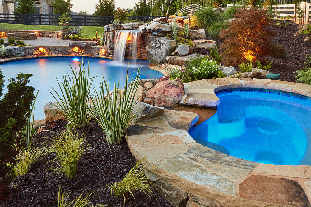 Boulder waterfall with grotto. Separate spa with Tennessee flagstone coping. Full landscape w lighting boulders and steps. $150