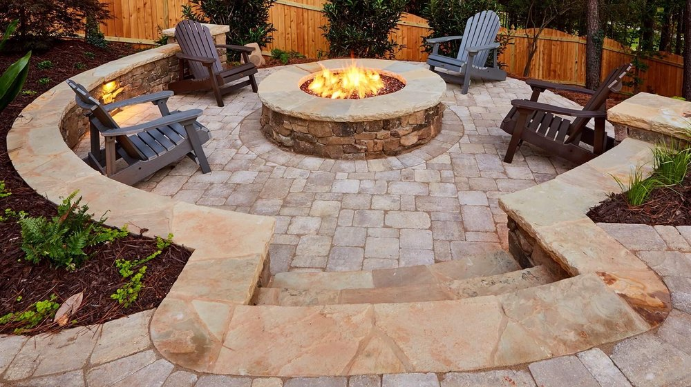 Circular rustic stack fire pit capped with Tennessee flagstone sunken below pool deck. Surrounded by a lighted stacked stone seat wall. $15 feature
