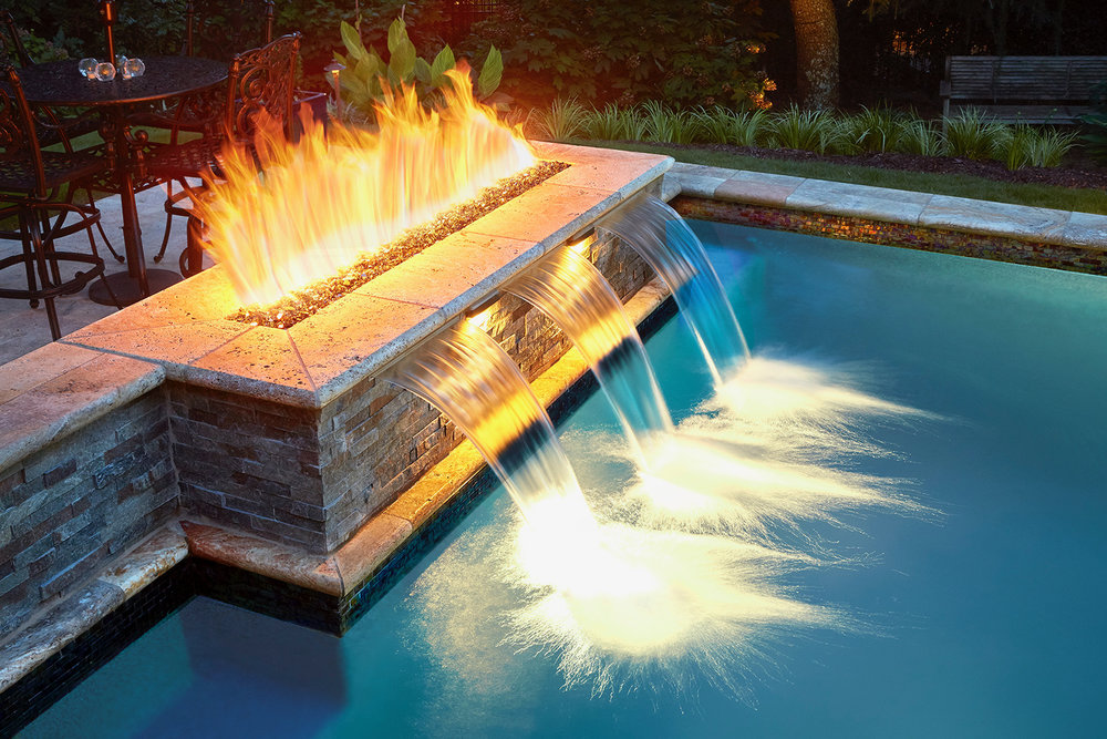 Fire + Water feature built into pool wall capped with Travertine. Reflective fire glass and sheer waterfalls. Reflects sun by day + fire at night $10 feature