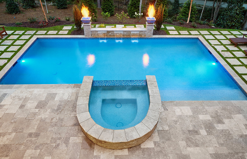 Oval raised spa. Glass tile spillway. Silver Travertine decking and accent wall with fire bowls and 3 sheer waterfalls $120