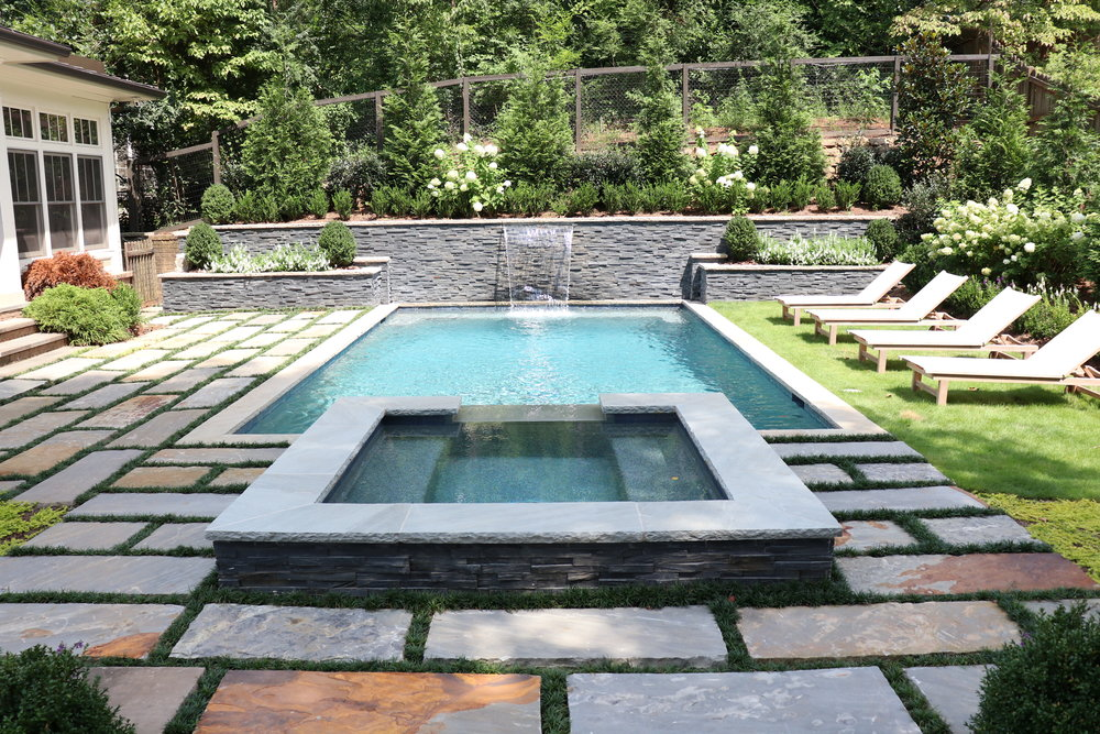 Raised spa. Stone spillway. Sheer waterfall hidden in black slate retaining wall. Living patio $120