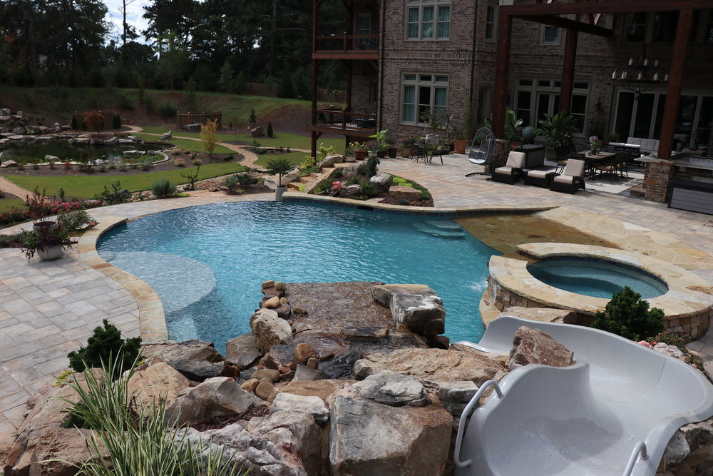 Beach entry. Infinity edge. Slide. Boulder waterfall and grotto. Raised spa w stone spillway. Flagstone coping. Kitchen built under existing patio $175