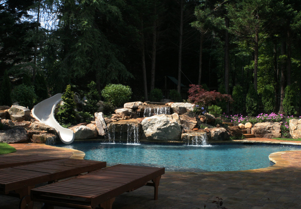 Disney waterfall w 10 tons of Tennessee boulders. Stone steps lead to a hidden bridge over the waterfall to the slide. Tennessee flagstone coping and concrete paver decking. Landscape and lighting. $120
