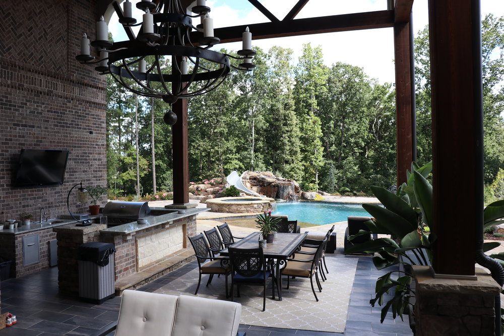 Outdoor kitchen custom built to align with house columns and existing patio. Includes grill, sink, fridge, cabinets, and bar top. $20 feature