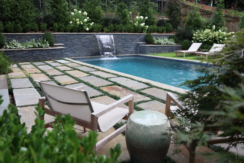 5' tall black slate retaining wall with 4' wide sheer waterfall and multi-level planters. Landscape Design: living patio on left and grass on right of the pool.