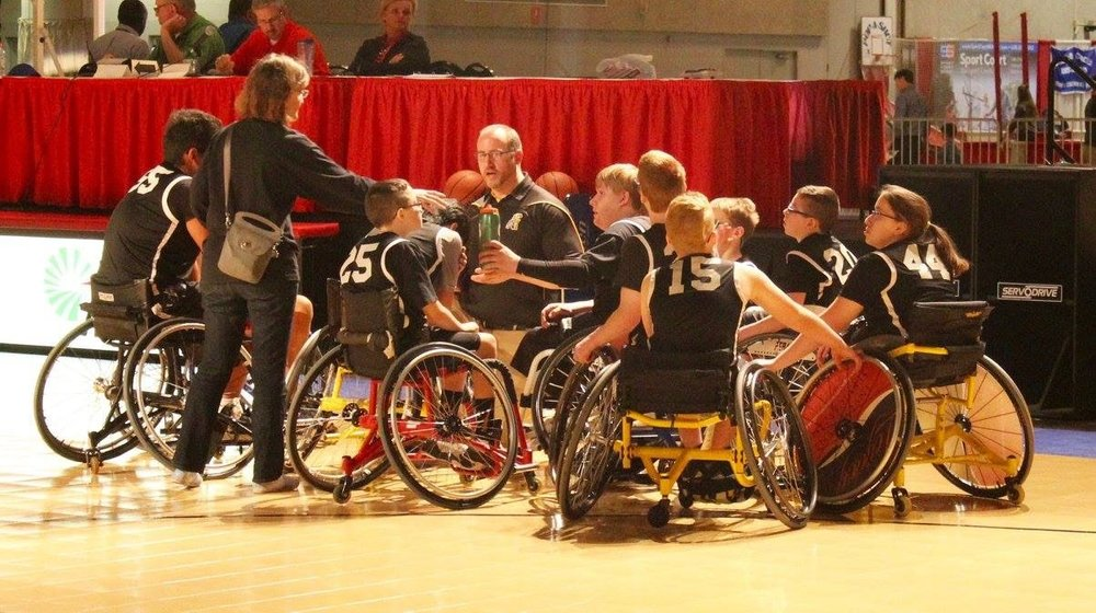 The Peoria Wildcats huddle up to start a game at the Peoria Civic Center for the IHSA State Wheelchair Basketball Tournament held during the March Madness Experience.