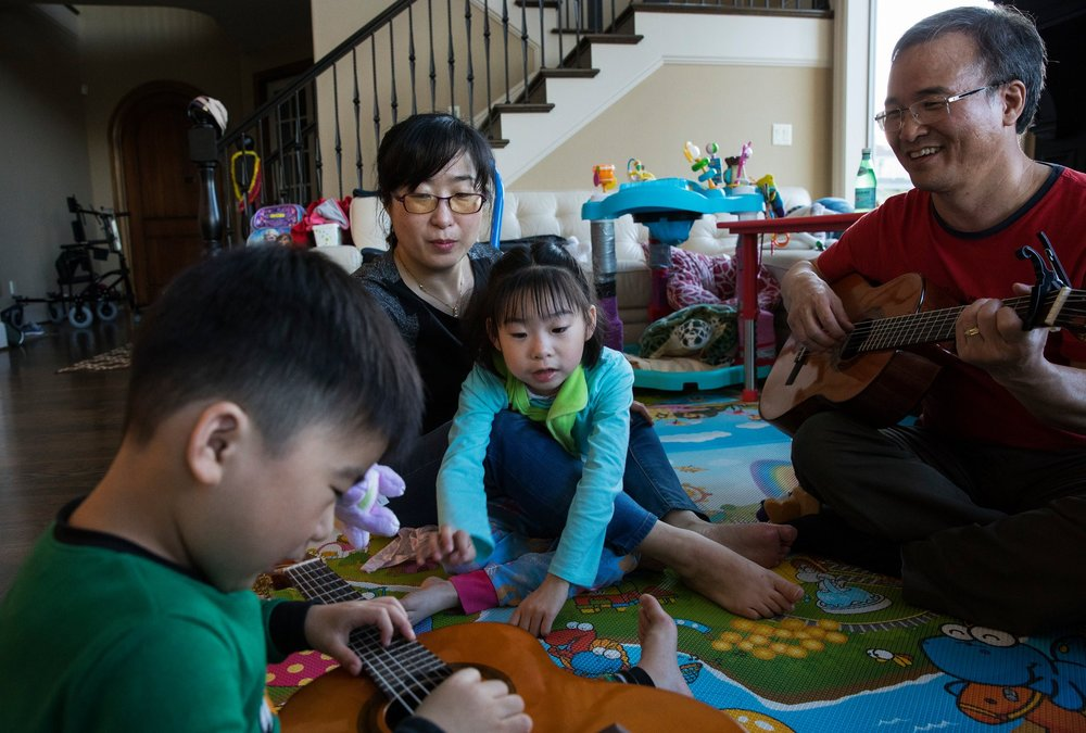 Music seems to calm Yuna, so her father Jae often plays guitar in the evenings. Yuna's brother, Joon, 5, helps as he can.CreditRuth Fremson/The New York Times