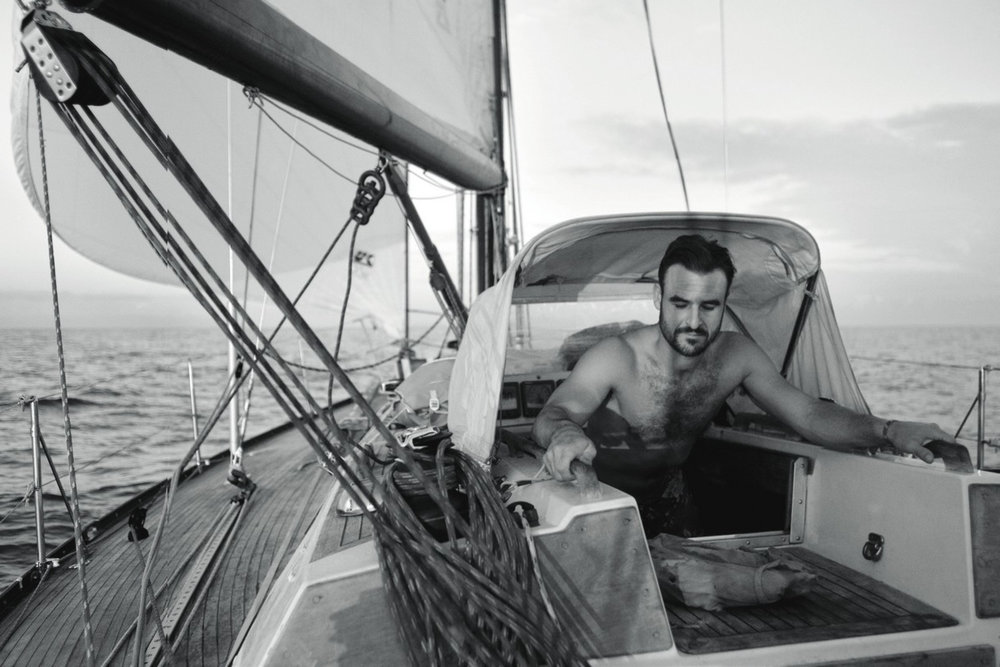 """Only assholes or admirals in the companionway""  Julian checks the weather before his morning shift, off Martinique, 2012, photo by Max Imrie"