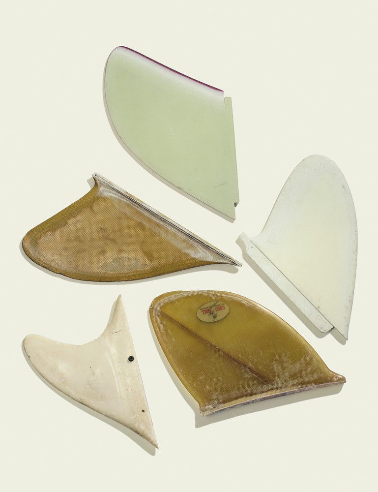 """Clockwise from top: a late '60s """"D"""" fin with foiled edge; a late '60s """"D"""" fin; an early '60s Greg Noll """"Chop Stick"""" fin; an early prototype fin for rental boards in Waikiki (note the side screw for mounting); a late '50s Greg Noll big wave fin."""