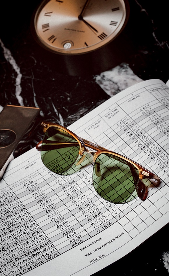 Executive I sunglasses in matte sycamore acetate with green-tinted lenses, antique gold ultra-thin titanium eye wire, and filigree detailing OLIVER PEOPLES vintage desk clock available at manoftheworld.com.  Helicopter pilot logbook Marzotto's own.