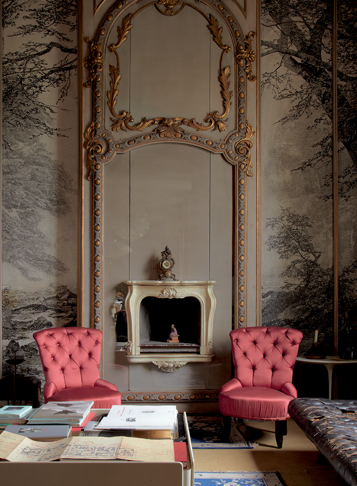 On the other side of the living room, a pair of pink silk slipper chairs sit astride a Louis XVI-style fireplace, designed by Mollino. A seated female figurine rules the hearth between fires.