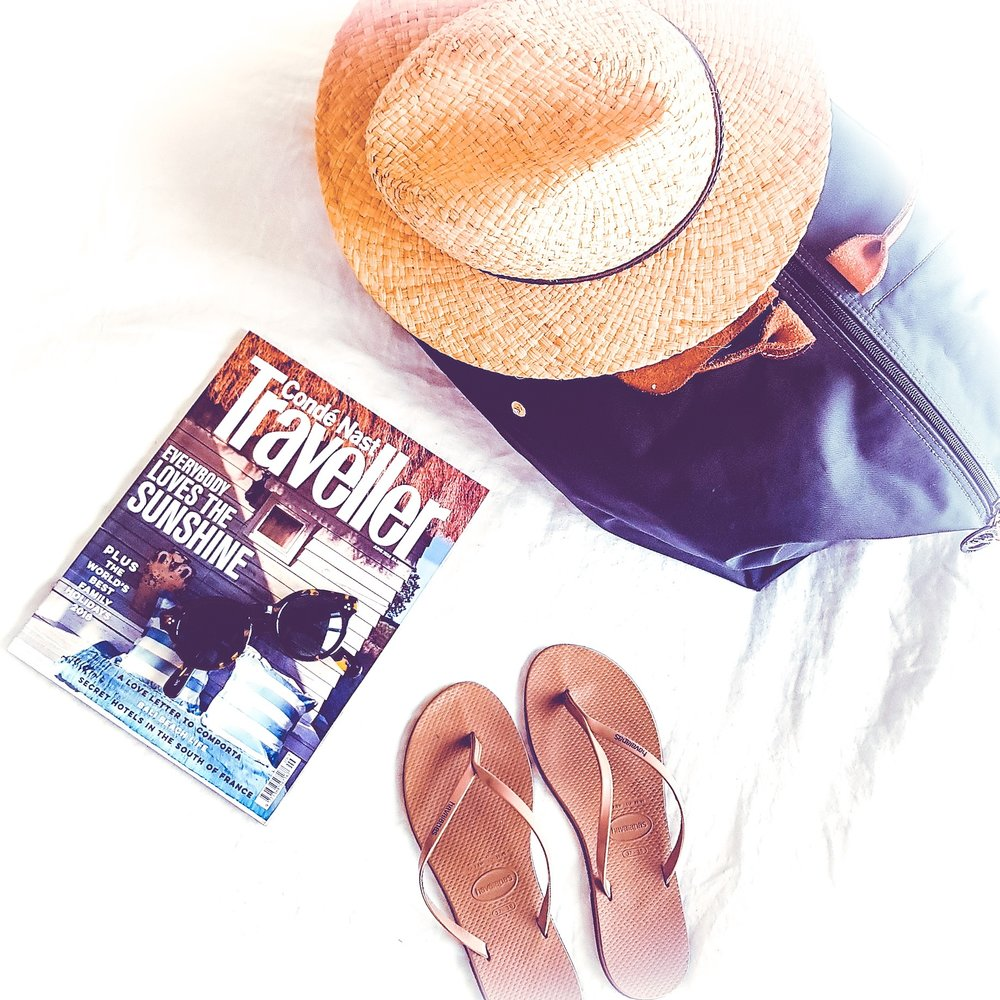 Minimalist Flat lay with straw hat on a Longchamp weekender bag. Sunglasses placed on Conde Nast traveller magazine and nude sandals on white bed cover.