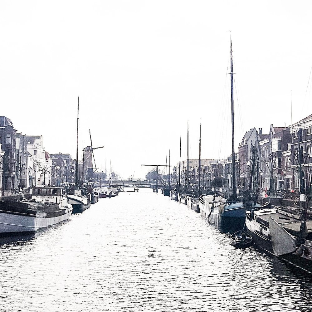 Black and white photo of Delfshaven by the river. Lots of boats, old houses make for a pretty picture