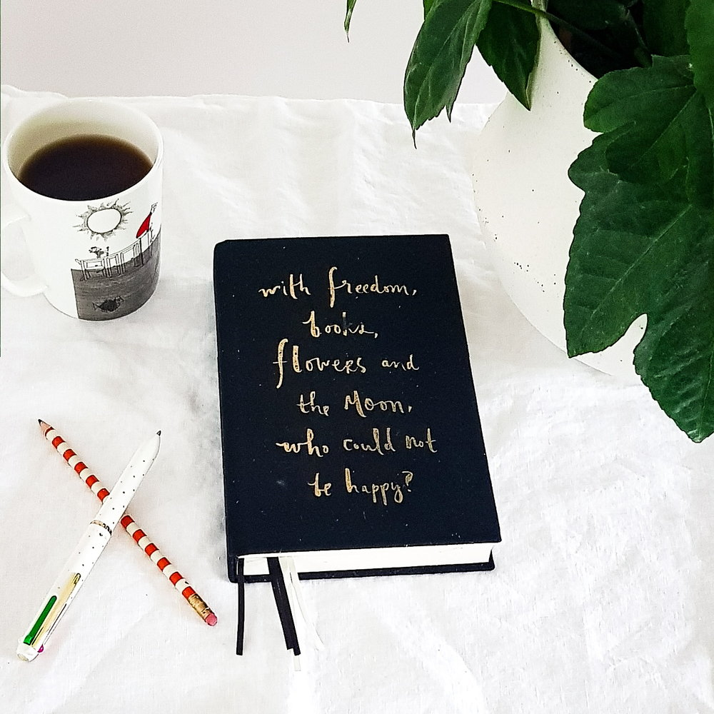 Flatlay to showJournal for shopping ban/ spending with pencil, pen beside it. Also mug with black coffee and pot plant. All on a white cotton table cloth. .