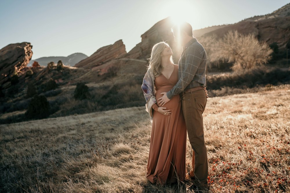red rocks maternity photoshoot couple in the sun embracing