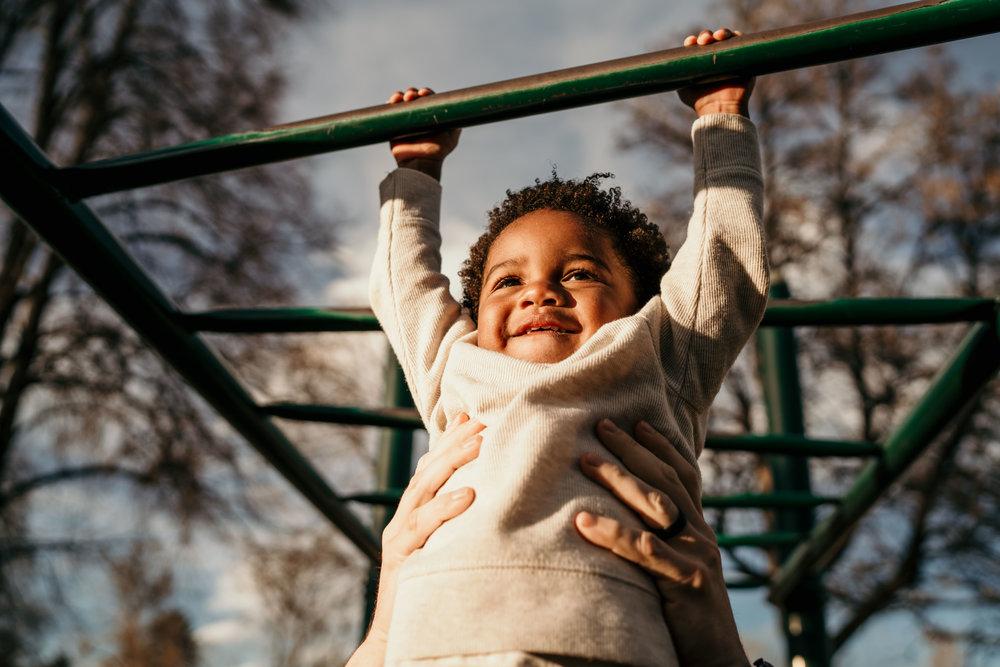 denver family photographers at city park kid on monkey bars