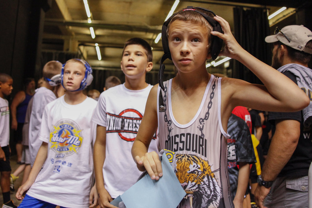 12-year-old Jake Justice, right, puts his gear on before he steps onto the mat for his first match of the day Saturday morning at the Show -Me State Games at the Hearnes Center. Jake has been wrestling since he was 7.