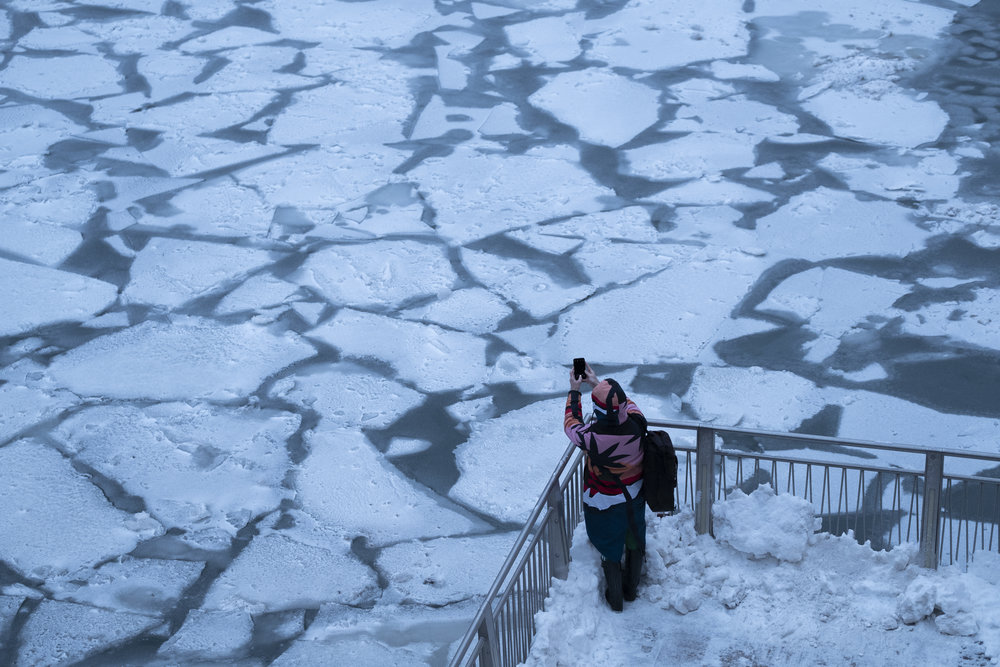 A pedestrian stops to take a photo by the Chicago River, on Tuesday. REUTERS/Pinar Istek