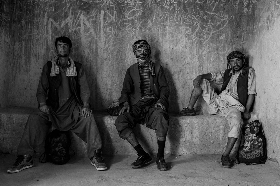More than 5000 Afghan and Pakistani refugees try to pass through the eastern Iranian border. Some will stay in Iran, others will go to Turkey and Greece. From left: Farugh, 22, Nikmuhammad, 21, and Mohammad, 25, wait for orders on their journey. Sistan and Baluchestan Province, Iran.  August 2017.