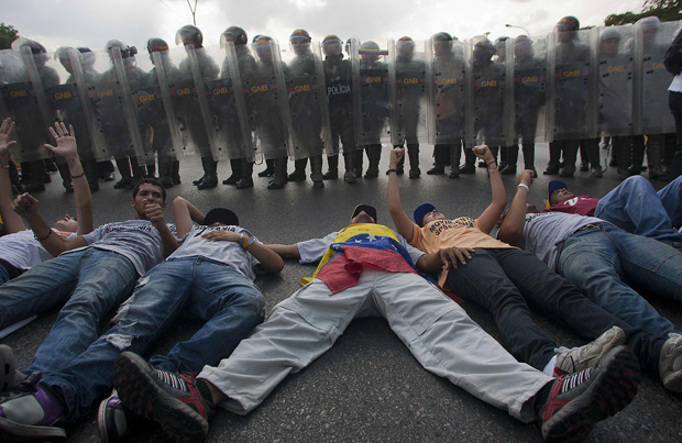 Simpatizantes de la oposición venezolana protestan frente a los policías antidisturbios en Caracas el 15 de abril de 2013. (AFP PHOTO/Geraldo Caso)