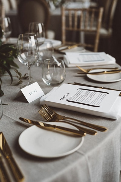 Place setting featuring gold cutlery.