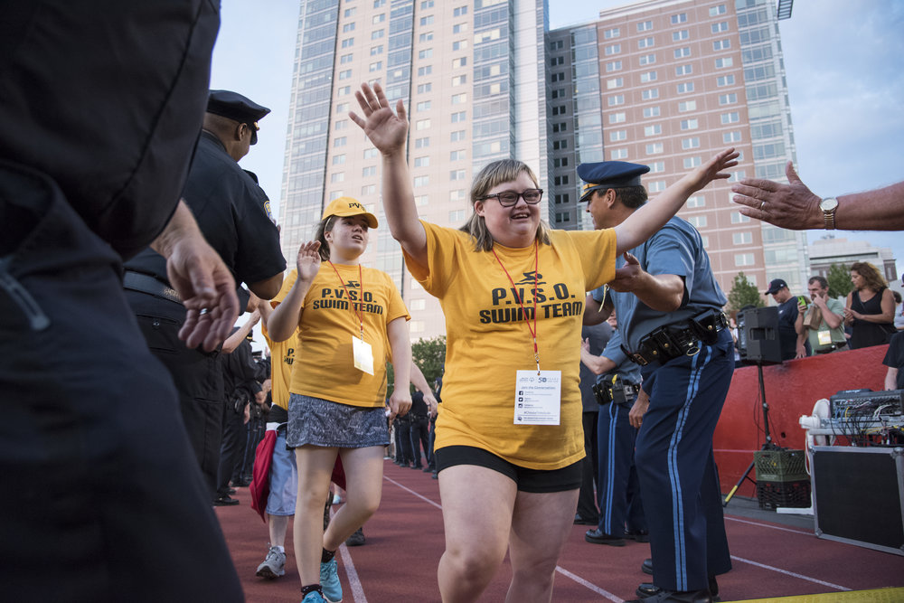Kayla Edgar, a Special Olympics athlete with the Pioneer Valley Aquatics Program, high-fives Boston police officers during the Parade of Athletes, a part of the 2018 Summer Games opening ceremony held on Boston University's Nickerson Field. This year marks the 50th anniversary of Special Olympics competition in the U.S.
