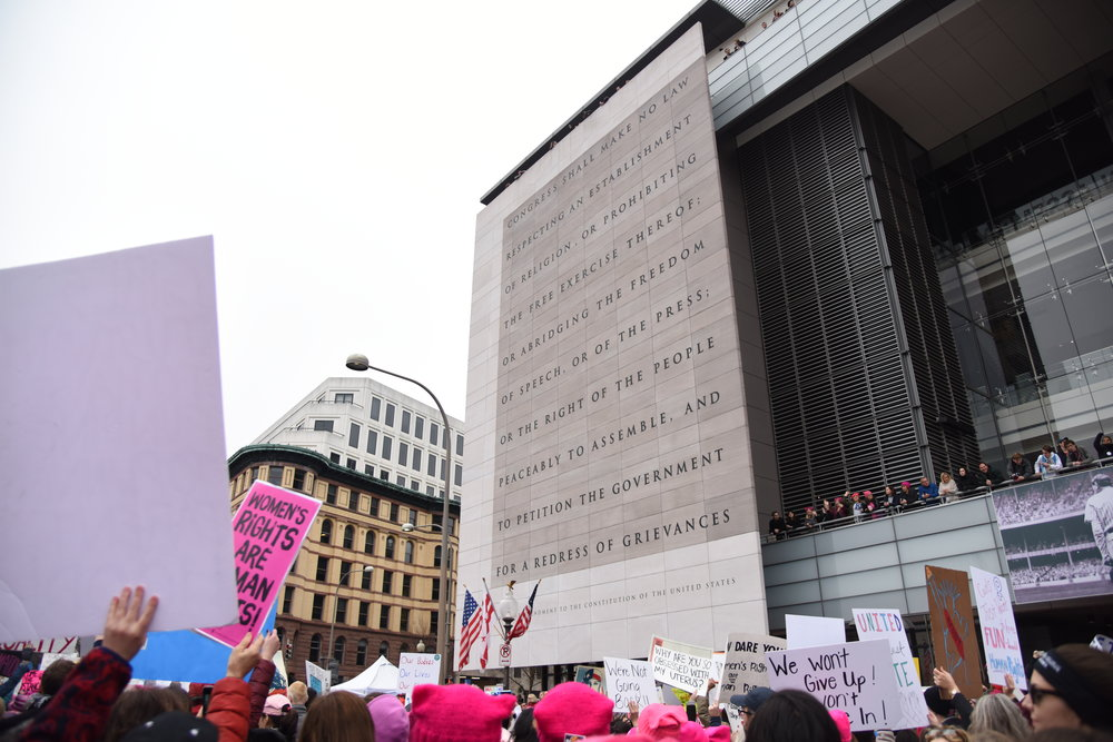 Marchers walk past the Newseum, the museum of news, in Washington D.C. during the Women's March on Washington, January 21 2017. Carved on the front of the museum is the first amendment to the constitution.
