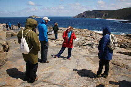 Geological Survey WA team member Lauren Burley (red Jacket) shares research techniques with participants in Geology in Action field session at the Gap, Albany