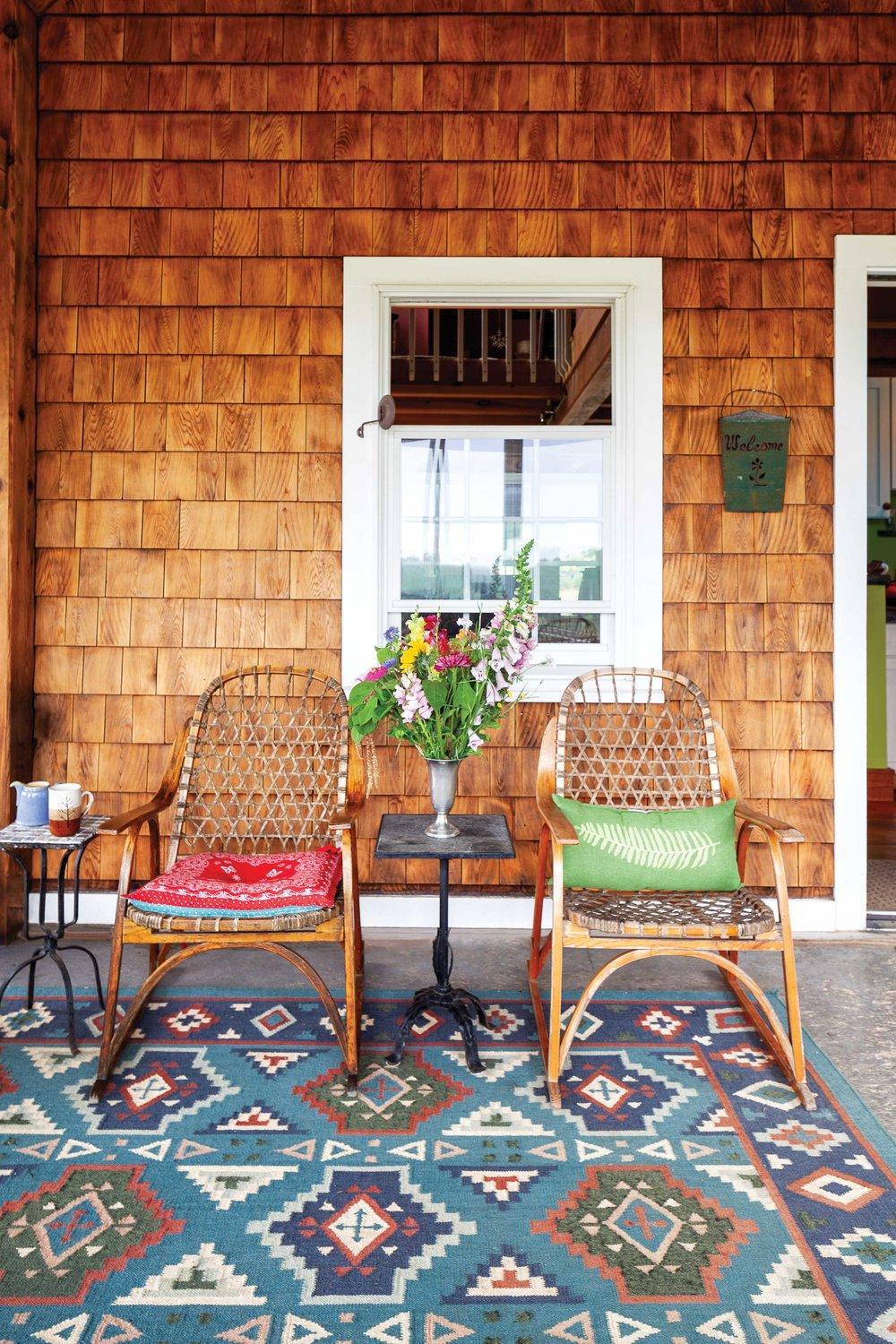 On the glassed-in porch, vintage chairs provide a cozy spot to enjoy the view.