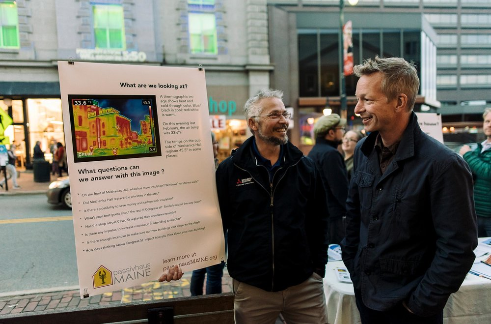 Dana Fischer and Chris Briley stand with a passivhausMAINE poster, designed to help the public understand the event, and interact with the organizers.