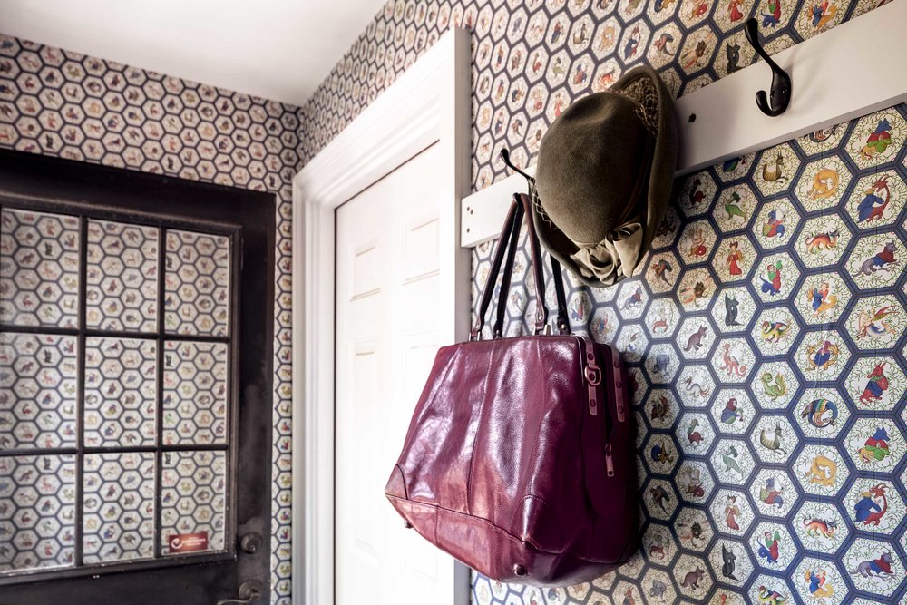 """Saiber typed """"medieval or Renaissance wallpaper"""" into a search engine and discovered Spoonflower, which produces custom wallpaper. They picked a design for their back hallway that incorporates monsters from medieval manuscripts. The red bag is from Spain, and the hat is one of several Saiber inherited from her grandmother."""