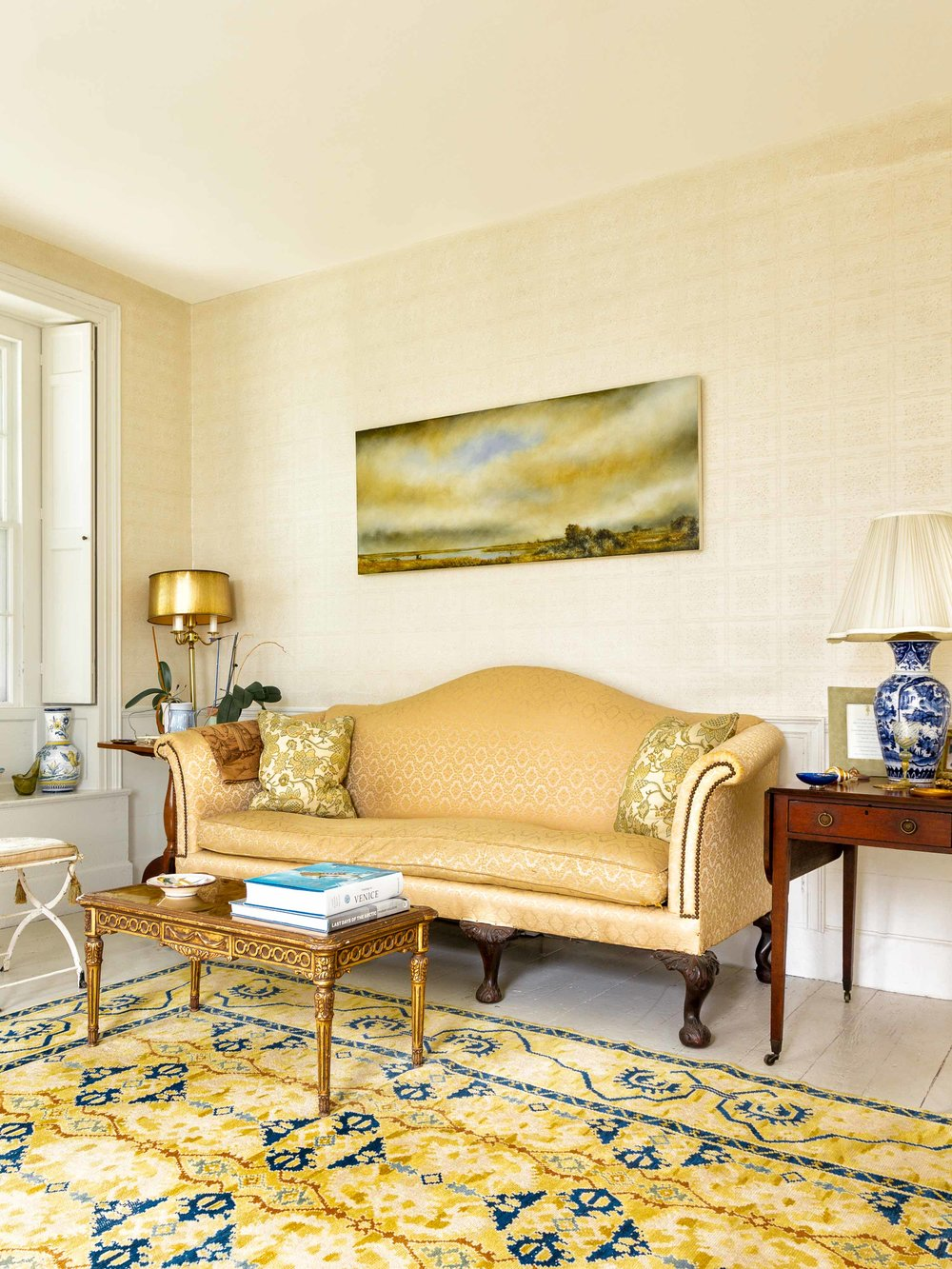 A landscape of a Delaware marsh by Peter Brooke hangs above the settee.