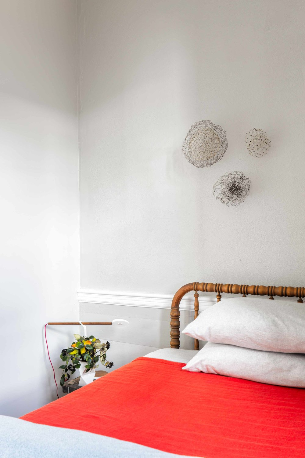 In the guest room, metalwork sculptures by Anna Hepler hang above an antique Jenny Lind spool bed.