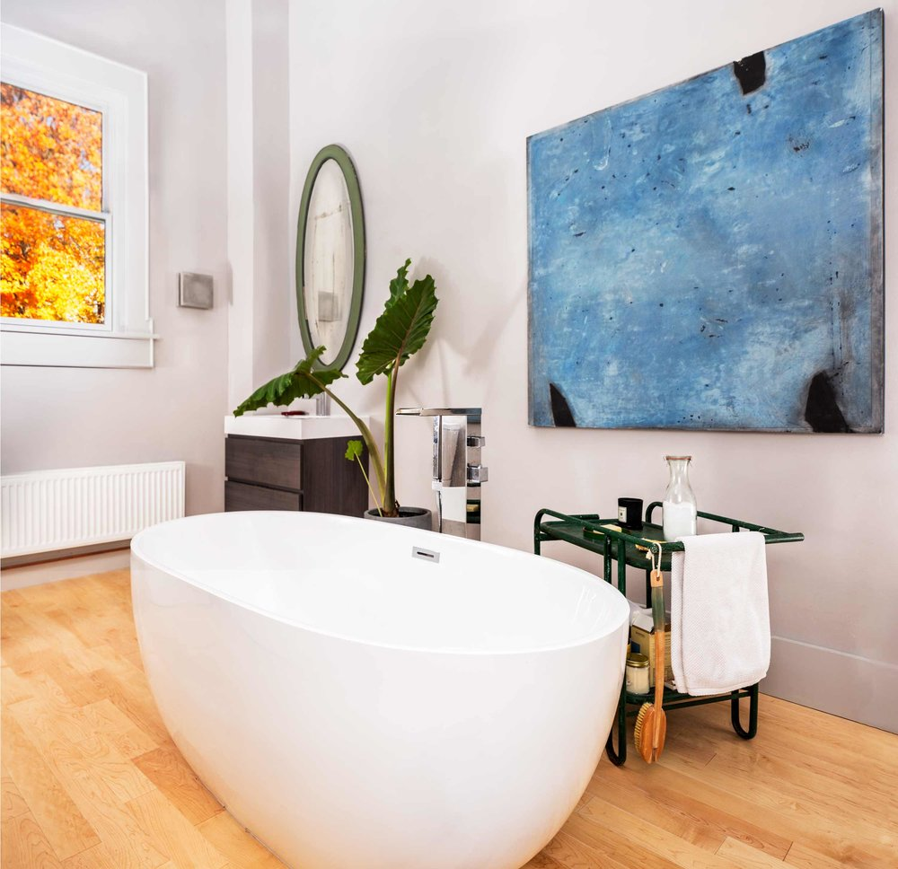 In McNeil's oasis of a bathroom, a freestanding tub and a painting by Greg Parker.