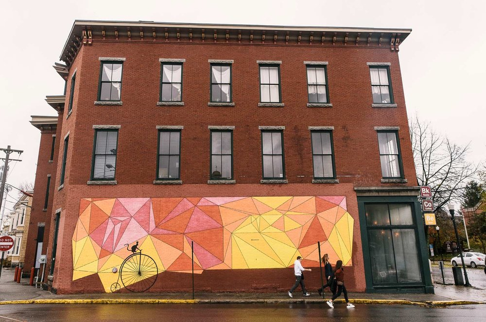 The property owners of the 265 Main Street building worked with Biddeford's Public Art Committee and the Heart of Biddeford, a nonprofit organization focused on downtown revitalization, to commission the mural by artist Julie Gray. Gray's artwork is a nod to the work of Friedrich Froebel, a German educationalist and originator of Kindergarten. Froebel's lessons stressed experimentation with simple forms, and the study of nature's geometry.