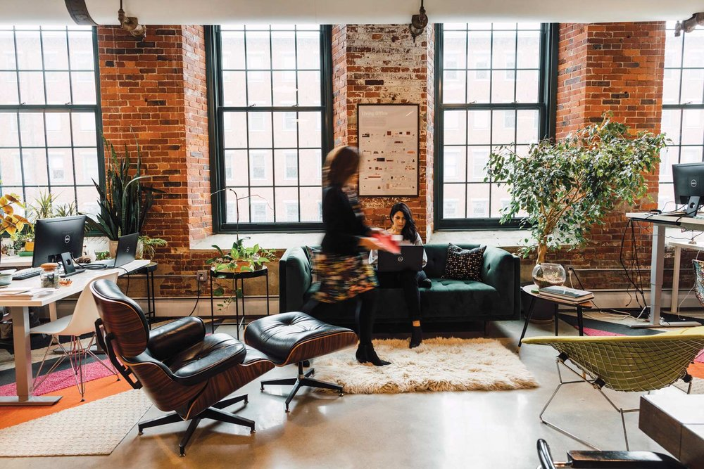 At their office in Saco Mill, some hallmarks of biophilic design are readily apparent: exposed brick, natural fibers, lots of plants, and plentiful light. A Chesterfield sofa, Eames chair and ottoman, and Bertoia diamond chair surround a wool Flokati rug.