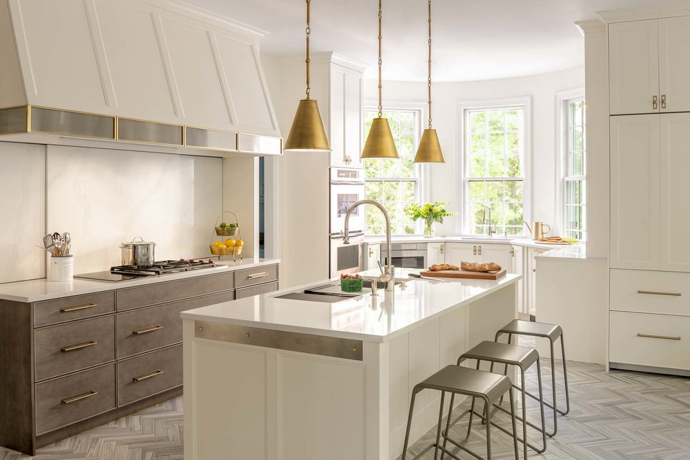 The new kitchen has two prep areas, as well as a clean-up area, to improve functionality. The layout is loosely based on the homeowners' kitchen in Chicago. Two different finishes for the white oak Rutt Cabinetry make the kitchen feel beachy yet sophisticated. The stools and stainless-steel strip on the island and kitchen hood add a slight industrial edge.