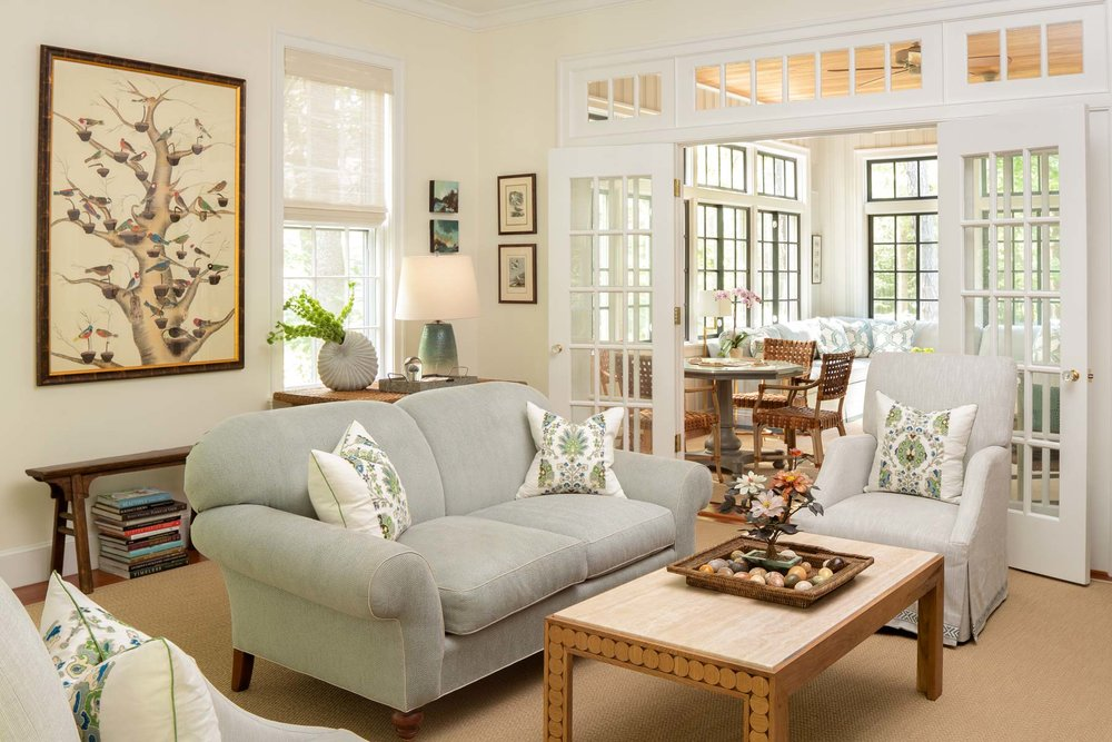 The living room has fifteen small framed Audubon prints, all of birds of Maine. The homeowners wanted another bird picture that wasn't an Audubon for the space. Fremont-Smith sourced the tree with birds, a large watercolor on silk, at Hurlbutt Designs. The room is entirely open to the neighboring sunroom but is still defined by clerestory windows and French doors. A turret space with built-in seating is just out of view to the left.