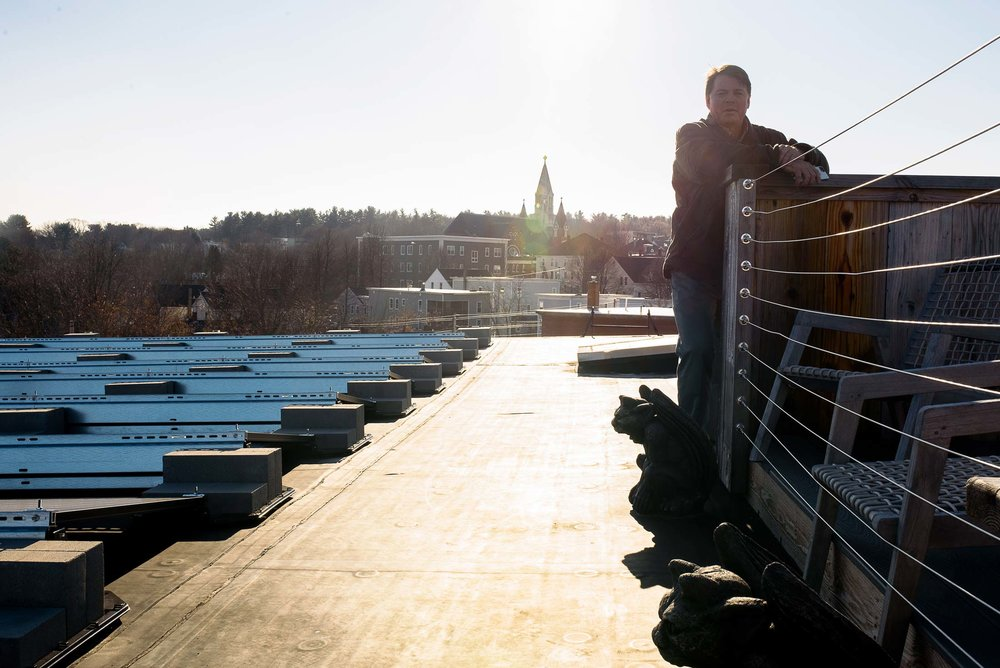 Scott Joslin, COO of the Pepperell Mill Campus, stands on the roof beside the solar array installed by ReVision Energy. Beyond, a bird's eye view of downtown Biddeford.