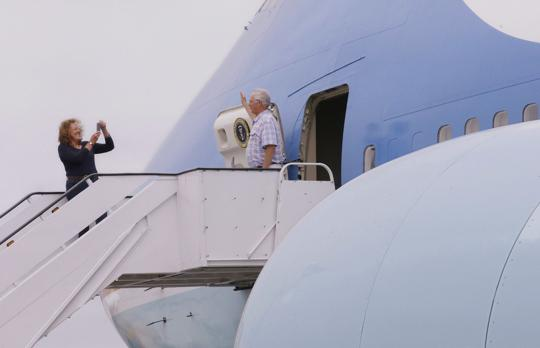 """In this Monday, Sept. 18, 2017 photo Julia More photographs Christopher Jenkins as he stands just outside of the front hatch of the """"Air Force One Experience,"""" a full-sized 747 replica of Air Force One which is now open to the public in North Kingstown, R.I. (AP Photo/Stephan Savoia)  Stephan Savoia"""