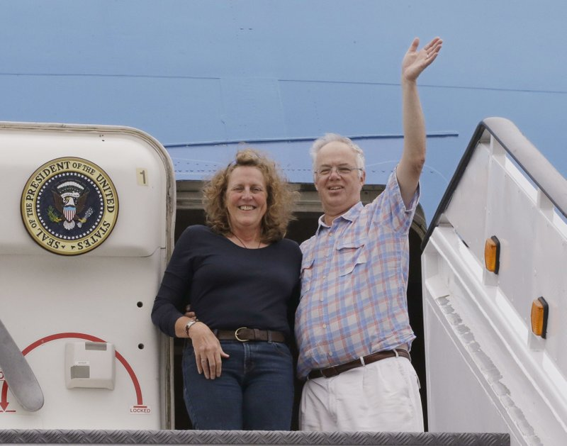"In this Monday, Sept. 18, 2017 photo Christopher Jenkins waves while he stands with Julia Mord as they mimic a presidential arrival for a friend who is making their picture during their tour of the ""Air Force One Experience,"" a full-sized 747 replica of Air Force One which is now open to the public in North Kingstown, R.I. (AP Photo/Stephan Savoia)"