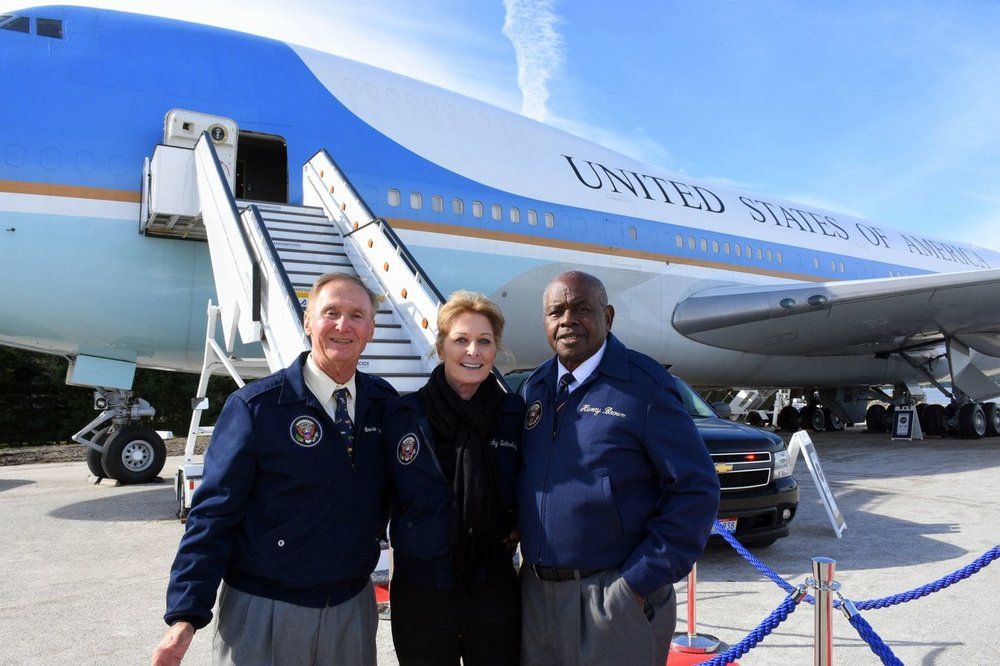 Air Force One flight attendants, from left, Howie Franklin, Becky Schulz and Henry Brown have more than 30 years of service aboard Air Force One among them. They are posing in front of the copy of the airplane at National Harbor. (Ann Cameron Siegal