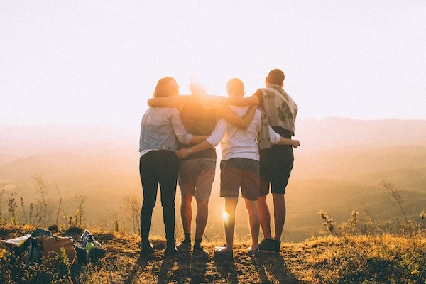 group of friends standing together at top of a hill at sunset